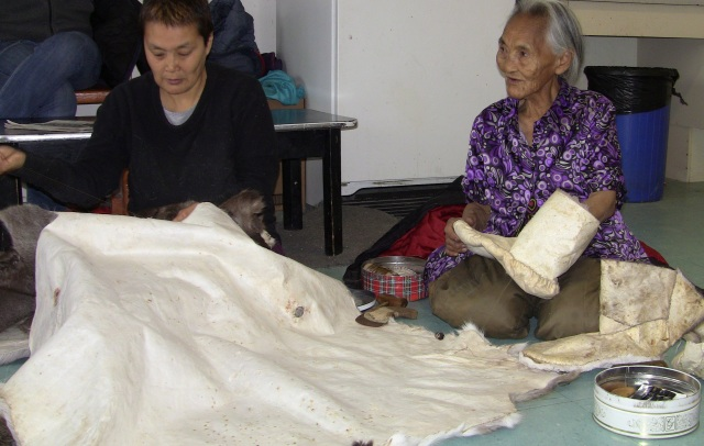Nanisiniq coordinator, Tamar Mukyunik and Inuit Elder, Eva Mukyungnik sew caribou skin clothing photo-unknown