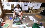 "Malkolm Boothroyd silk screening ""put people before polluters"" t-shirts."