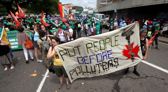 Karen Rooney and Daniel T'Seleie hold a banner during the Global Day of Action March in Durban.